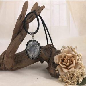 Ciondolo con pietra grigia e cristalli neri